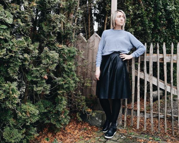 Lederrock-Outfit mit Oversize-Pullover und Schnürschuhe